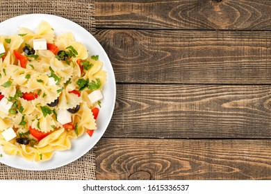 Pasta primavera with colorful vegetable on wooden desk
