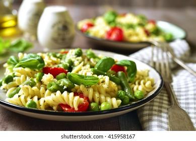 Pasta primavera on a vintage plates on wooden background.