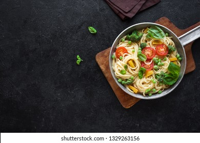 Pasta Primavera. Spaghetti pasta with vegetables and basil, top view, copy space. Vegetarian seasonal pasta primavera recipe.