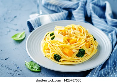 Pasta with pumpkin, spinach and walnuts. toning. selective focus