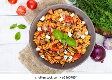 Pasta Radiatori with chicken, mushrooms, cherry tomatoes, feta cheese and tomato sauce on a white wooden background. Top view.