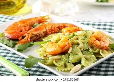 Pasta with red prawns and rocket pesto with almonds on complex backgruind