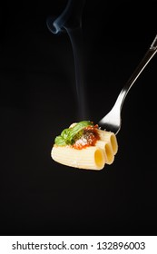 Pasta Rigatoni with Rag���¹, Parmesan and basil on fork, black background
