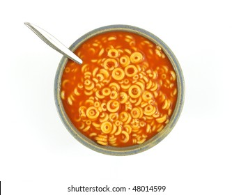 Pasta rings with tomato sauce and spoon in bowl
