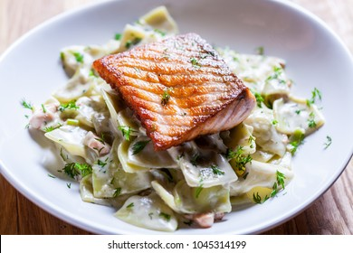 Pasta with roasted salmon in  sour cream leeks and dill. Fresh home made pasta. Delicious dish. beautifull fried salmon on top of home made pasta. Italian dish. Fine dining. Beautiful ingredients.
