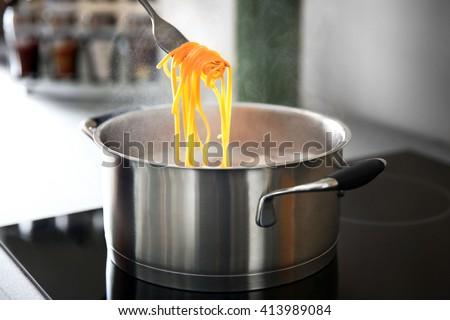 Pasta rolled on fork over pan on stove in the kitchen