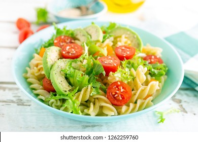 Pasta salad with avocado, fresh tomato, pepper and lettuce, top view