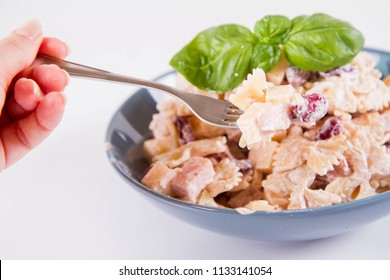 Pasta salad with cheese, ham, kidney beans and mayonnaise eaten with a fork