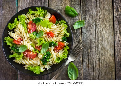 Pasta salad with cherry tomatoes and broccoli, top view