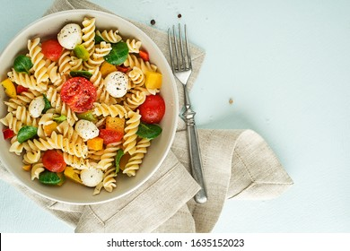 Pasta salad with mozzarella cheese and vegetables. Healthy pasta meal.