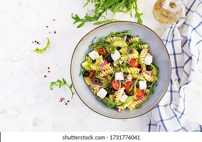 Pasta salad with tomato, avocado, black olives, red onions and cheese feta. Mediterranean cuisine. Top view, overhead, flat lay