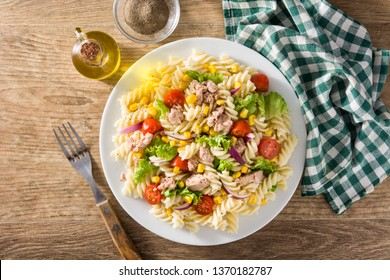Pasta salad with vegetables and tuna on wooden table. Top view