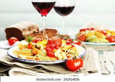 Pasta salad with vegetables and two glasses of red wine on wooden table background