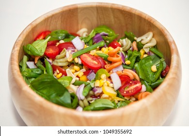 Pasta salad in a wooden bowl, with tomatoes, sweetcorn, onion, spinach