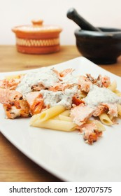 Pasta with salmon and basil sauce on wood table