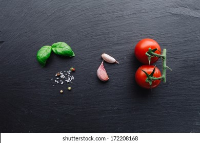 Pasta sauce ingredients concept on black slate background viewed from top