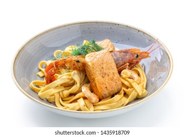 Pasta in sauce and with squid and a piece of fish. Italian dish.
