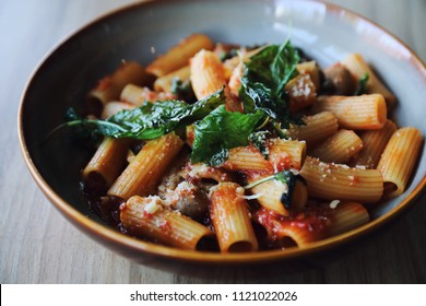 Pasta with sausage in tomato sauce on wood background , italian food