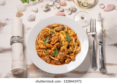 Pasta with sea fruit in white plate on a white wooden background, soft light, top view. Spaghetti ai frutti di mare, seafood mediterranean gastronomy