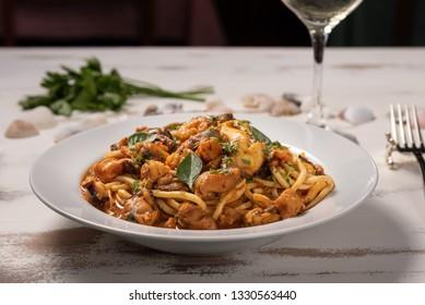Pasta with sea fruit in white plate on a white wooden background, soft light, angle view. Spaghetti ai frutti di mare, seafood mediterranean gastronomy