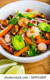 Pasta with seafood and vegetables in white bowl