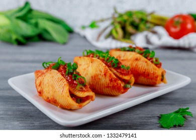 pasta shells stuffed with minced beef meat with herbs and tomato sauce
