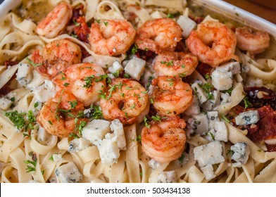 Pasta with shrimp, cheese and sauce on wood background. Close up.