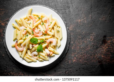 Pasta with shrimp and mint leaves. On black rustic background