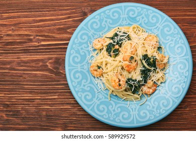 pasta with shrimps, spinach and parmesan on wooden table background