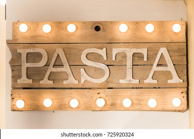 Pasta sign made of wooden planks and light bulbs on top and bottom