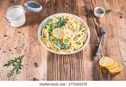 Pasta with a sour cream lemon and herbs on wooden boards. Top view Tagliatelle - spaghetti on dish