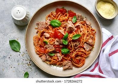 Pâtes de spaggeti au thon et à la sauce tomate dans un bol sur ardoise grise, pierre ou béton. Vue supérieure avec espace de copie.