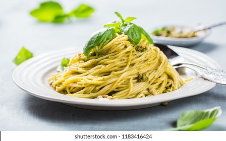 Pasta spaghetti with basil cream and cheese. Top view on grey stone table. Vegetarian vegetable pasta.