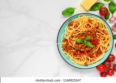 pasta spaghetti bolognese on a blue plate on white marble table. healthy food. view from above with copy space
