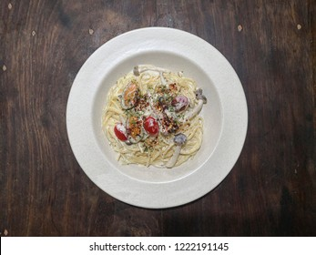 Pasta or spaghetti carbonara consists of tomato cherry, whipping cream and mussels, added of chilli flakes and dried parsley on the top of wooden table.