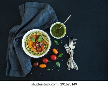 Pasta spaghetti with pesto sauce, basil, slow-roasted cherry-tomatoes in rustic metal bowl on dark grunge backdrop, top view, copy space