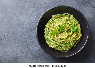 Pasta spaghetti with pesto sauce in black bowl. Grey background. Copy space. Top view.