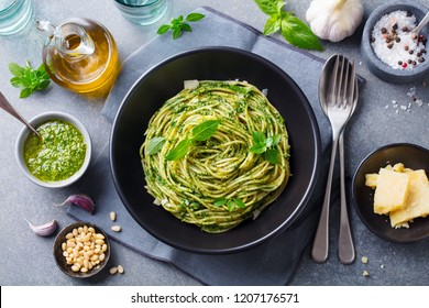Pasta spaghetti with pesto sauce and fresh basil leaves in black bowl. Grey background. Top view.