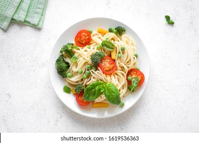 Pasta Spaghetti Primavera, vegetarian pasta dish with vegetables tomato, broccoli, green pea, bell pepper and basil leaves, top view, copy space.