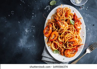 Pasta spaghetti with shrimps and tomato sauce served on plate on dark background.