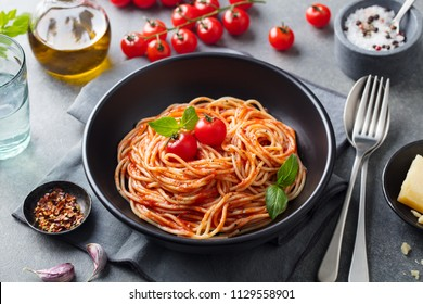 Pasta, spaghetti with tomato sauce in black bowl on grey background.