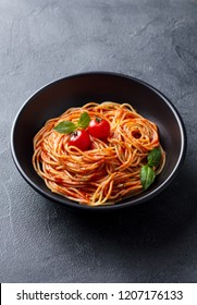 Pasta, spaghetti with tomato sauce in black bowl. Grey stone background.