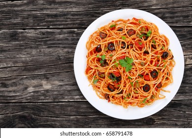 Pasta spaghetti with tomato sauce, capers and olives on plate on dark wooden table, traditional Italian food, view from above