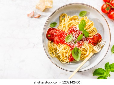 Pasta spaghetti with tomato sauce and cheese parmesan served on plate on marble table background. Closeup with copy space.
