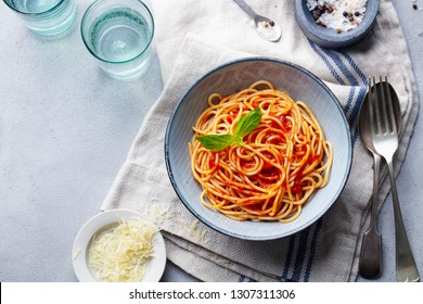Pasta, spaghetti with tomato sauce and fresh basil in a bowl. Grey background. Top view. Copy space.