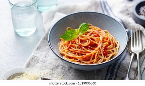 Pasta, spaghetti with tomato sauce and fresh basil in a bowl. Grey background.  Copy space.