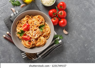 Pasta, spaghetti with tomato sauce in gray bowl on grey background. Copy space.