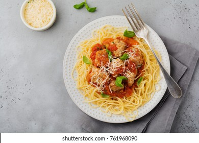 Pasta spaghetti with tomato sauce, parmesan cheese, basil and meatballs on white ceramic plate on gray concrete or stone background. Selective focus. Top view.