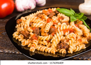 Pasta (spirals pasta)  Bolognese. Tagliatelle with minced meat  on a black plate on a dark wooden background..