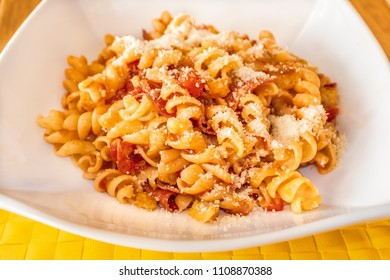 Pasta spirals with salami and tomato in a white dish on a yellow place mat